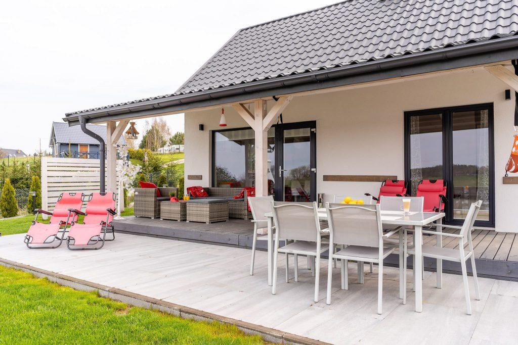 Domek Czerwony stolik i leżaki na tarasie